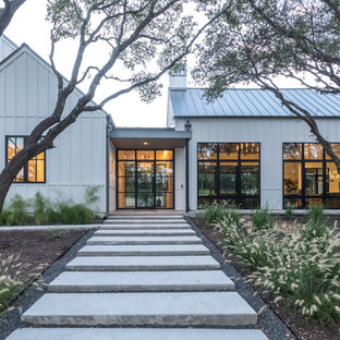 Example of a cottage white two-story vinyl exterior home design in Austin with a metal roof