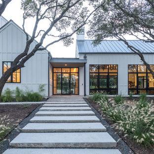 Modelo de fachada de casa blanca, campestre, de dos plantas, con revestimiento de vinilo, tejado a dos aguas y tejado de metal