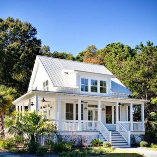 Imagen de fachada de casa blanca, tradicional, pequeña, de dos plantas, con revestimiento de aglomerado de cemento, tejado a dos aguas y tejado de metal
