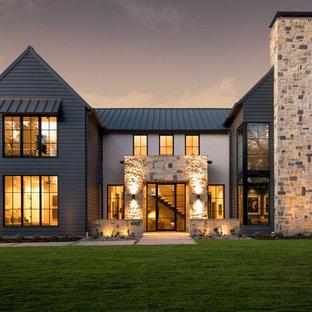 Idee per la facciata di una casa unifamiliare multicolore country a due piani con rivestimenti misti, tetto a capanna e copertura in metallo o lamiera