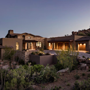 Inspiration for a southwestern brown one-story mixed siding exterior home remodel in Phoenix with a mixed material roof