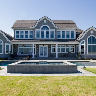 Example of a coastal gray two-story wood exterior home design in Jacksonville with a gambrel roof