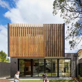 Design ideas for a mid-sized contemporary two-storey multi-coloured house exterior in Melbourne with mixed siding and a flat roof.