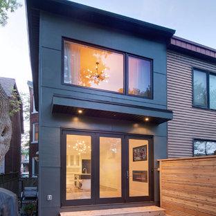 Foto på ett litet funkis grått hus, med två våningar och fiberplattor i betong