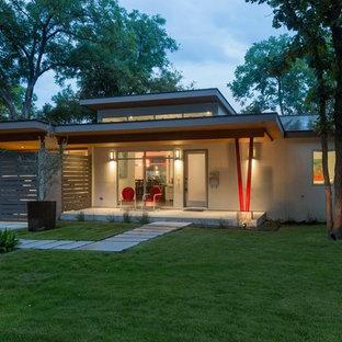 Esempio della facciata di una casa unifamiliare piccola grigia contemporanea a un piano con rivestimento in stucco, tetto piano e copertura in metallo o lamiera