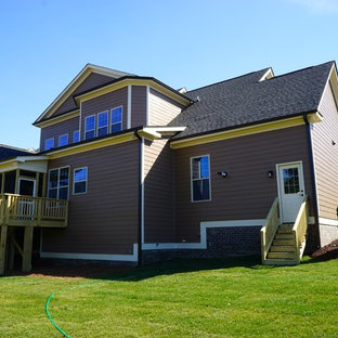 ローリーのコンテンポラリースタイルのおしゃれな家の外観 (混合材サイディング、茶色い外壁、半切妻屋根) の写真