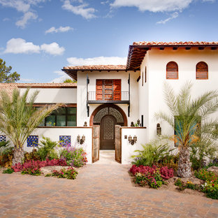 Inspiration for a huge mediterranean white split-level stucco exterior home remodel in Austin with a hip roof