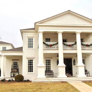 Cette image montre une très grand façade de maison blanche traditionnelle à un étage avec un toit à deux pans, un toit en tuile et un revêtement en stuc.