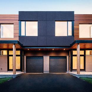 Esempio della facciata di una casa bifamiliare contemporanea con rivestimento in legno