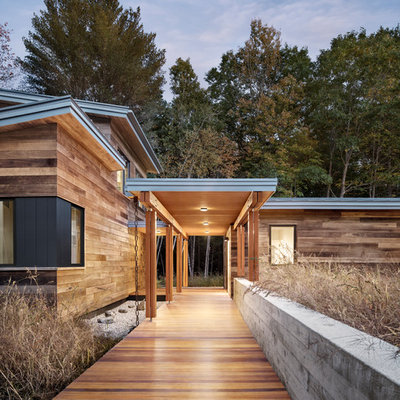 Large trendy brown one-story wood house exterior photo in Portland Maine