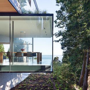 Пример оригинального дизайна интерьера: трехэтажный фасад дома в стиле модернизм с облицовкой из стекла и плоской крышей