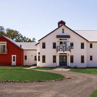 Imagen de fachada blanca, campestre, de tamaño medio, de dos plantas, con revestimiento de madera y tejado a doble faldón