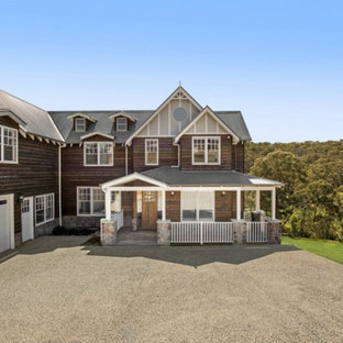 Large mountain style three-story wood house exterior photo in Melbourne with a gambrel roof and a metal roof