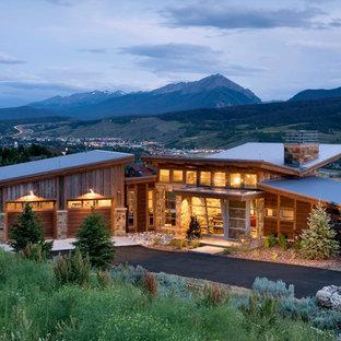 Aménagement d'une façade de maison montagne de plain-pied avec un toit papillon.