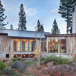 Example of a large mountain style wood exterior home design in Sacramento with a metal roof