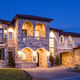 Large mediterranean three-story stone exterior home idea in Austin