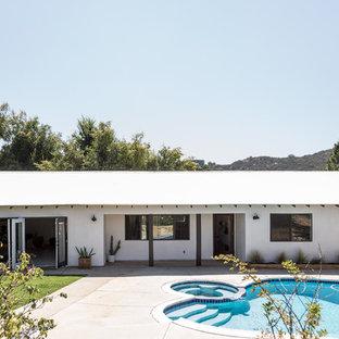 Inspiration pour une façade de maison blanche sud-ouest américain de taille moyenne et de plain-pied avec un revêtement en stuc.