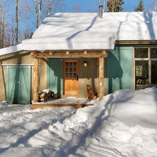 Ispirazione per la facciata di una casa piccola beige rustica a un piano con rivestimento in legno e tetto a capanna