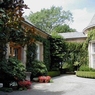 Foto på ett stort vintage beige hus, med två våningar, mansardtak och tak i shingel