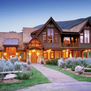 Large mountain style two-story wood exterior home photo in Denver with a mixed material roof