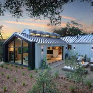 Inspiration för lantliga svarta hus, med allt i ett plan, metallfasad, platt tak och tak i metall