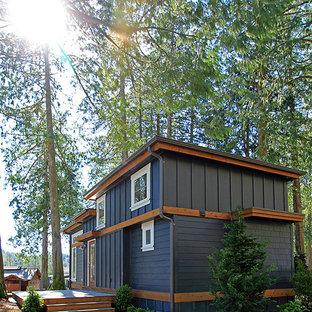 Small craftsman blue one-story concrete fiberboard flat roof idea in Seattle