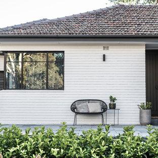 Foto de fachada de casa gris, vintage, de una planta, con revestimiento de ladrillo, tejado a dos aguas y tejado de teja de barro