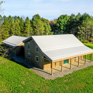 Inspiration for a mid-sized country two-storey brown house exterior in New York with wood siding and a metal roof.