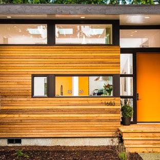 Diseño de fachada multicolor, actual, de tamaño medio, de una planta, con revestimiento de madera y tejado plano