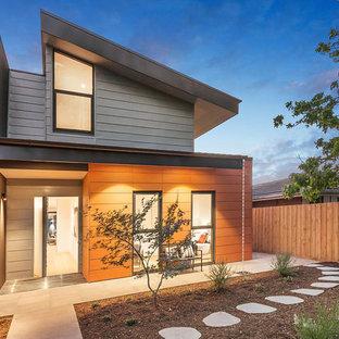 メルボルンのコンテンポラリースタイルのおしゃれな家の外観 (混合材サイディング、マルチカラーの外壁、半切妻屋根、デュープレックス、金属屋根) の写真
