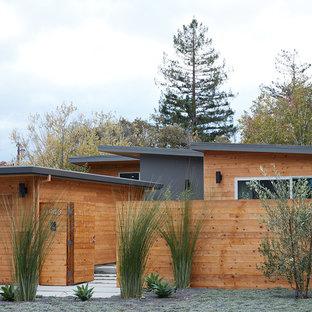 サンフランシスコの中くらいのミッドセンチュリースタイルのおしゃれな家の外観 (木材サイディング、茶色い外壁) の写真