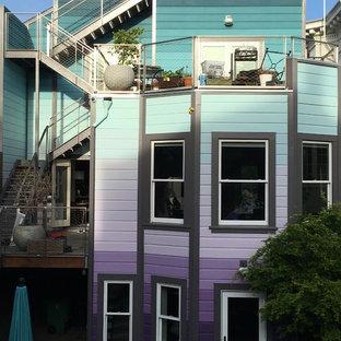 Aménagement d'une grand façade de maison de ville violet éclectique à deux étages et plus avec un revêtement en stuc et un toit plat.