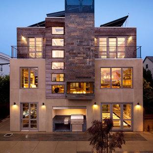 Esempio della facciata di una casa ampia marrone contemporanea a tre piani con rivestimenti misti e tetto piano
