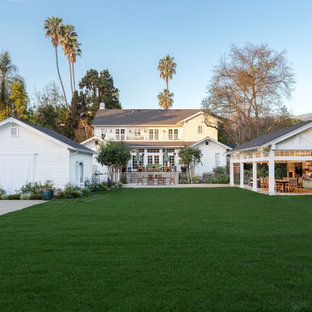Elegant white two-story exterior home photo in Los Angeles with a shingle roof