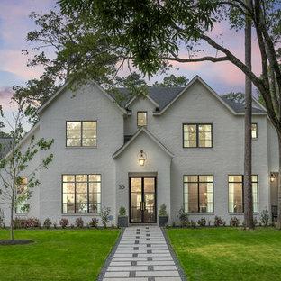 Esempio della facciata di una casa unifamiliare ampia bianca classica a due piani con rivestimento in mattoni, tetto a capanna e copertura a scandole
