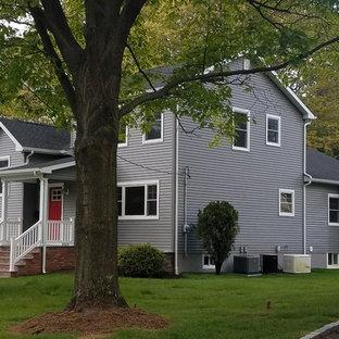 Modelo de fachada de casa gris, retro, de tamaño medio, a niveles, con revestimiento de vinilo, tejado a dos aguas y tejado de teja de madera