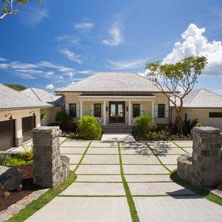Foto de fachada beige, tropical, de una planta, con tejado a cuatro aguas