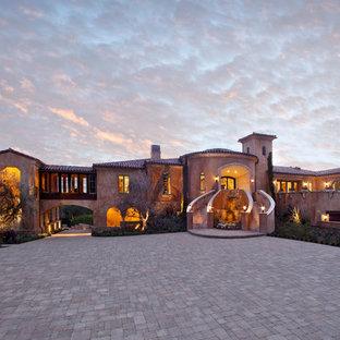 Ispirazione per la facciata di una casa beige mediterranea a piani sfalsati con rivestimento in adobe