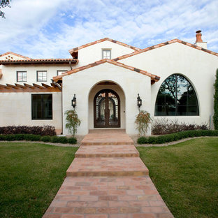 Mediterranean two-story stucco exterior home idea in Austin with a tile roof