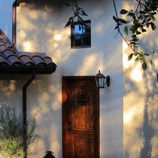 Inspiration for a mid-sized mediterranean beige two-story stucco exterior home remodel in Santa Barbara with a tile roof