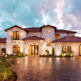 Example of a large tuscan white two-story stucco exterior home design in Austin with a hip roof