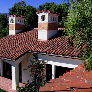Modelo de fachada de casa blanca, mediterránea, de tamaño medio, de una planta, con revestimiento de estuco, tejado a la holandesa y tejado de teja de barro