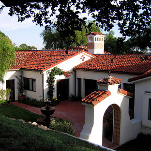 Inspiration for a mid-sized mediterranean white one-story stucco house exterior remodel in Santa Barbara with a clipped gable roof and a tile roof