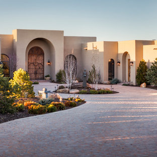 Example of a huge tuscan beige one-story stucco exterior home design in Albuquerque