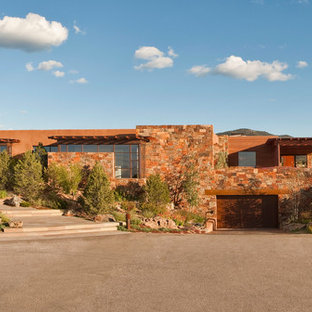 Inspiration for a large southwestern brown one-story stone exterior home remodel in Albuquerque with a metal roof