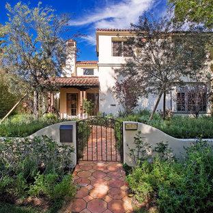 Diseño de fachada de casa blanca, mediterránea, de dos plantas, con revestimiento de estuco, tejado a dos aguas y tejado de teja de barro