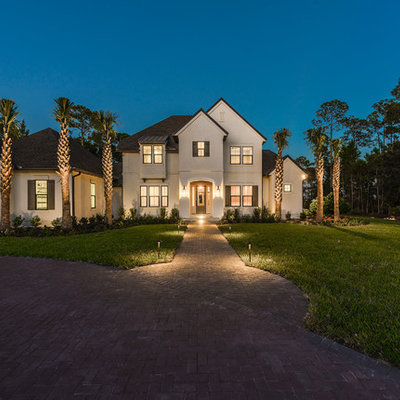 Large traditional beige two-story stucco exterior home idea in Jacksonville with a shingle roof