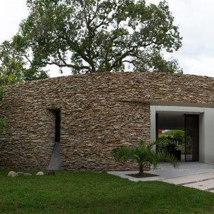 Diseño de fachada de casa beige, ecléctica, de tamaño medio, de una planta, con revestimiento de piedra, tejado plano y tejado de varios materiales