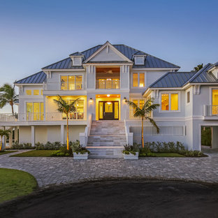 Tropical gray two-story mixed siding exterior home idea in Tampa with a hip roof and a metal roof