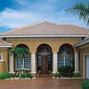 Imagen de fachada beige, mediterránea, de tamaño medio, de una planta, con revestimiento de estuco y tejado a cuatro aguas